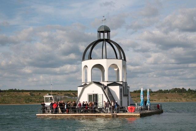 """Tagungsteilnehmer auf der """"Vineta"""", einem schwimmenden Kunstobjekt in Anlehnung an die überbaggerte Kirche von Magdeborn, das auf dem Störmthaler See an die für die Kohlengewinnung im Tagebau Espenhain umgesiedelten Ortschaften erinnern soll"""